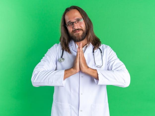 Zufriedener erwachsener männlicher arzt mit medizinischem gewand und stethoskop mit brille, der die hände zusammenhält und die kamera isoliert auf grüner wand betrachtet