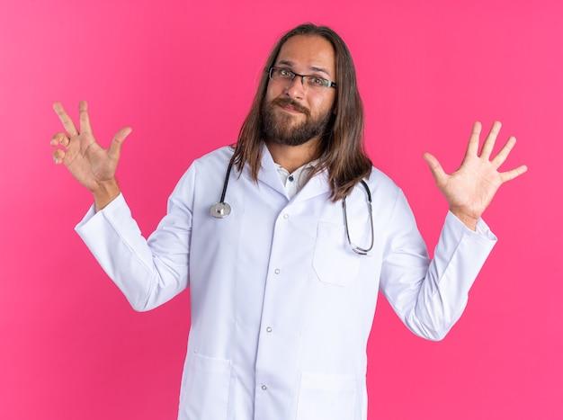 Zufriedener erwachsener männlicher arzt mit medizinischem gewand und stethoskop mit brille, die acht mit den händen zeigt
