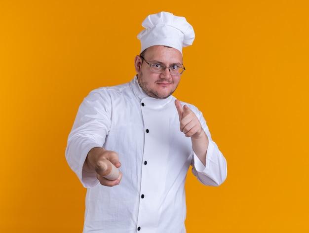 Zufriedener erwachsener männlicher koch mit kochuniform und brille, der mit finger und nudelholz nach vorne schaut und zeigt, isoliert auf oranger wand mit kopierraum