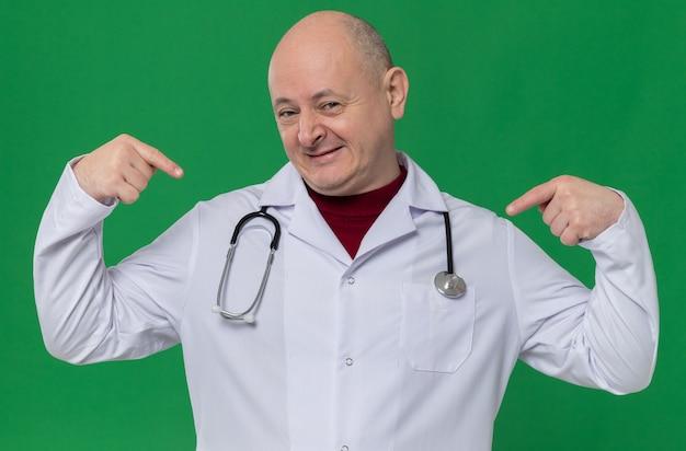 Zufriedener erwachsener mann in arztuniform mit stethoskop, das auf sich selbst zeigt