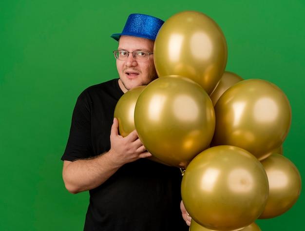 Zufriedener erwachsener slawischer mann in optischer brille mit blauem partyhut hält heliumballons