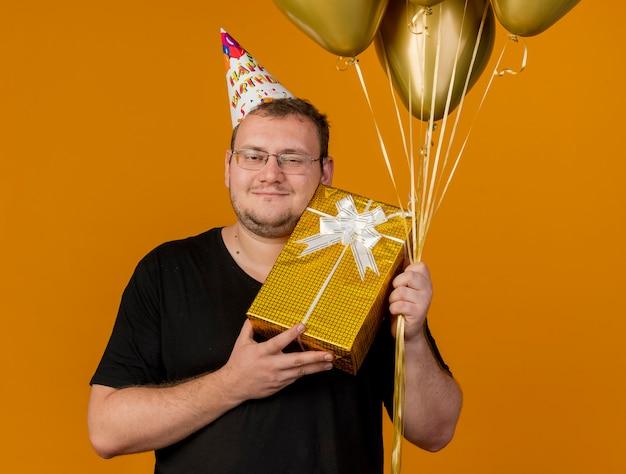 Zufriedener erwachsener slawischer mann in optischer brille mit geburtstagskappe hält heliumballons und geschenkbox