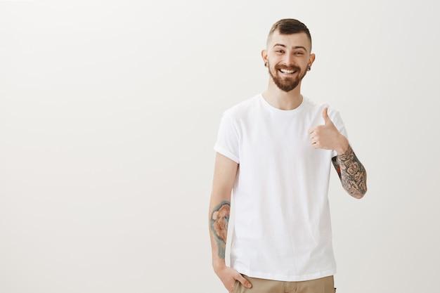 Zufriedener fröhlicher hipster mit tätowierungen, die daumen hoch zeigen, gut gemacht