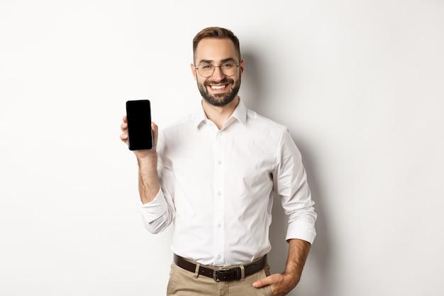 Zufriedener geschäftsmann, der mobilen bildschirm zeigt, stolz lächelnd, über weißem hintergrund stehend.