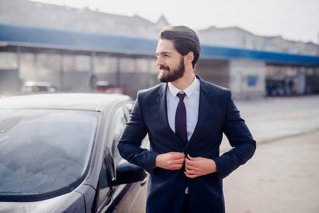 Zufriedener geschäftsmann, der neben seinem sauberen auto aufwirft. autowaschkonzept.