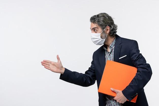 Zufriedener geschäftsmann im anzug und hält seine dokumente mit chirurgischer maske und begrüßt jemanden auf weißer oberfläche