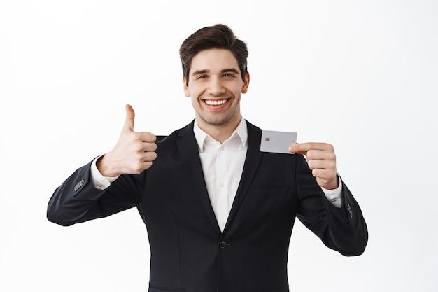 Zufriedener geschäftsmann zeigt daumen hoch und kreditkarte der copyspace-bank, steht im schwarzen anzug gegen weiße wand und empfiehlt