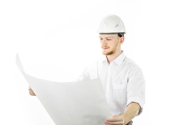 Zufriedener, gutaussehender ingenieur im schutzhelm, der mit blaupausen arbeitet