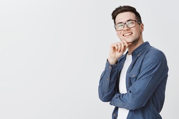 Zufriedener gutaussehender mann mit brille, der in der oberen rechten ecke zufrieden aussieht und entzückt lächelt