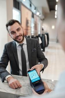 Zufriedener hübscher junger mann im anzug mit zahlungsanwendung beim bezahlen mit smartphone im bekleidungsgeschäft