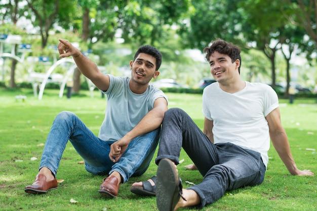 Zufriedener indischer kerl, der mit dem finger auf baum zeigt