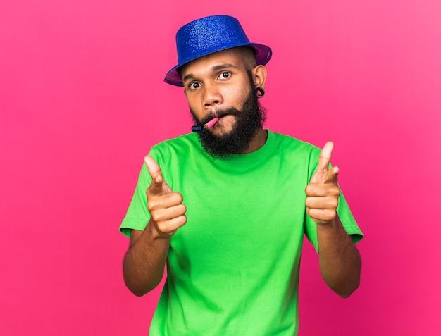 Zufriedener junger afroamerikaner mit partyhut, der partypfeife bläst, zeigt auf die kamera