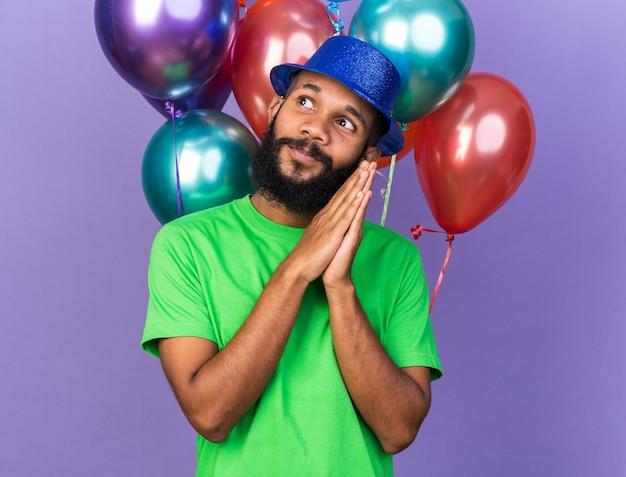 Zufriedener junger afroamerikanischer typ mit partyhut, der vor ballons steht und händchen hält