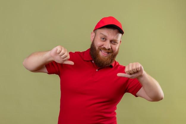 Zufriedener junger bärtiger lieferbote in roter uniform und mütze, die auf sich selbst lächelnd zeigen