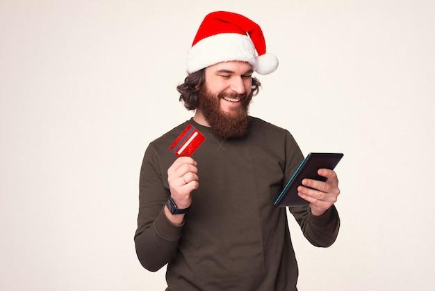 Zufriedener junger bärtiger mann bezahlt seine weihnachtseinkäufe online mit kreditkarte auf einem tablet.
