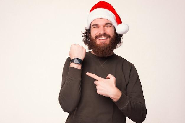 Zufriedener junger bärtiger mann zeigt auf seine intelligente armbanduhr.