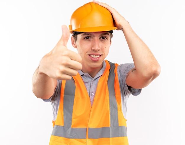 Zufriedener junger baumeister in uniform, der den daumen nach oben zeigt und die hand auf den kopf legt, isoliert auf weißer wand