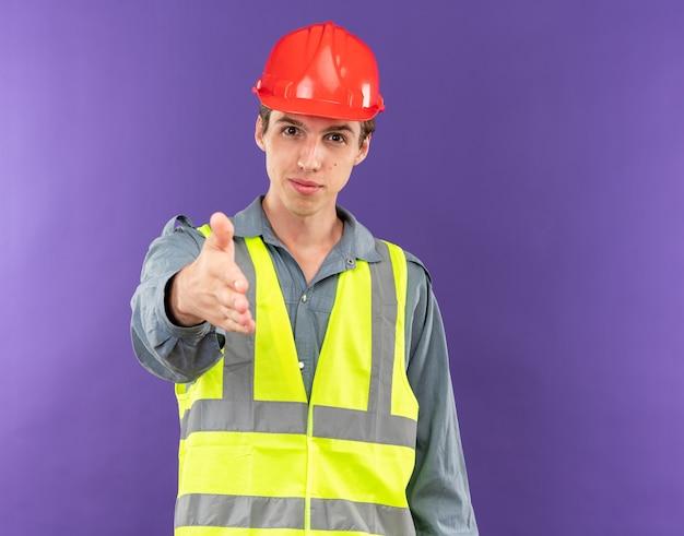 Zufriedener junger baumeister in uniform, der die hand isoliert auf blauer wand ausstreckt