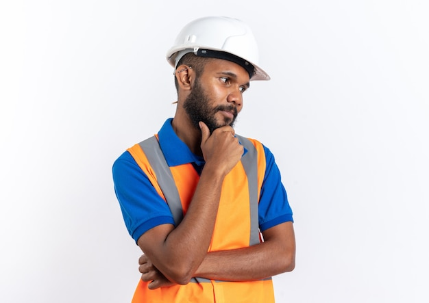 Zufriedener junger baumeister in uniform mit schutzhelm, der das kinn hält und seitlich isoliert auf weißer wand mit kopienraum schaut