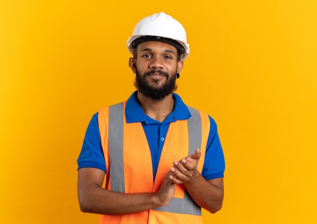 Zufriedener junger baumeister in uniform mit schutzhelm, der die hände zusammenhält, isoliert auf oranger wand mit kopierraum