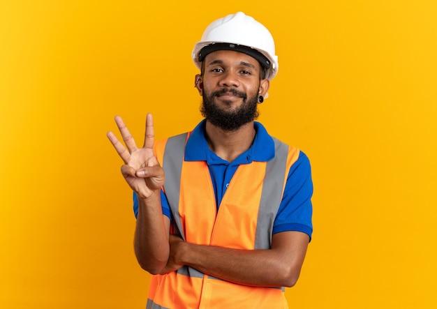 Zufriedener junger baumeister in uniform mit schutzhelm, der drei mit fingern gestikuliert, die auf orangefarbener wand mit kopierraum isoliert sind?