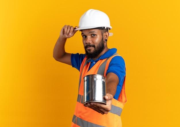Zufriedener junger baumeister in uniform mit schutzhelm, der ölfarbe isoliert auf oranger wand mit kopierraum hält