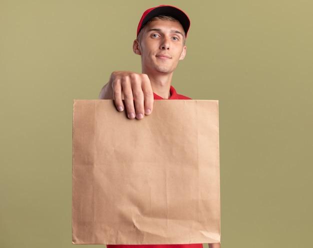 Zufriedener junger blonder lieferjunge hält papierpaket isoliert auf olivgrüner wand mit kopierraum
