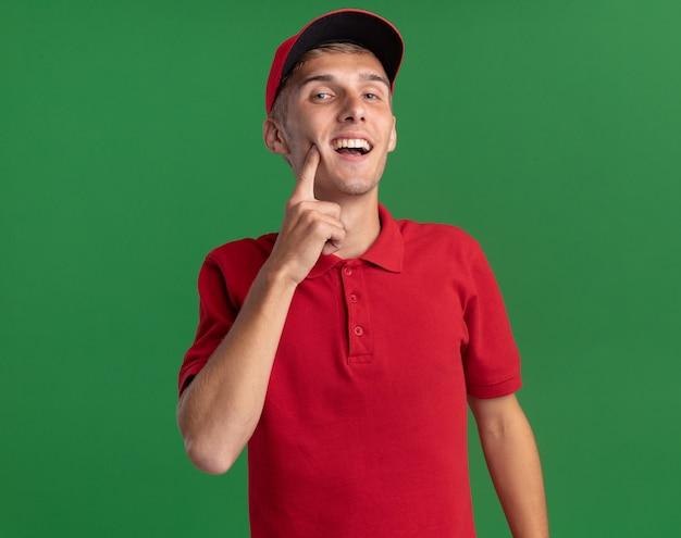 Zufriedener junger blonder lieferjunge legt finger auf gesicht isoliert auf grüner wand mit kopienraum