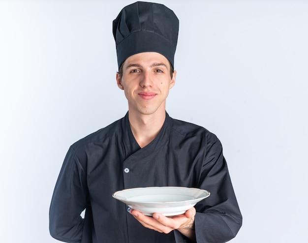 Zufriedener junger blonder männlicher koch in kochuniform und mütze, der die hand hinter dem rücken hält und auf die kamera schaut, die die platte in richtung kamera ausstreckt, isoliert auf weißer wand