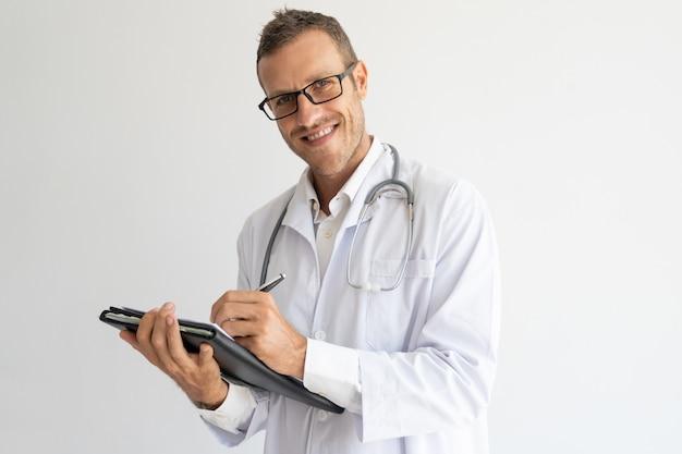 Zufriedener junger doktor, der anmerkungen auf papier macht