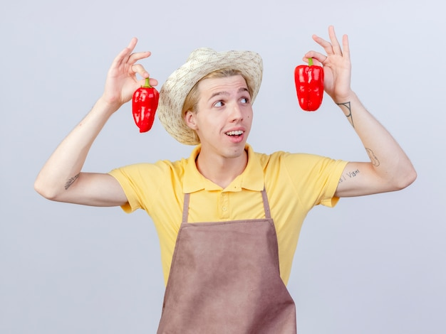 Zufriedener junger gärtnermann mit overall und hut, der rote paprika zeigt, die fröhlich lächelt