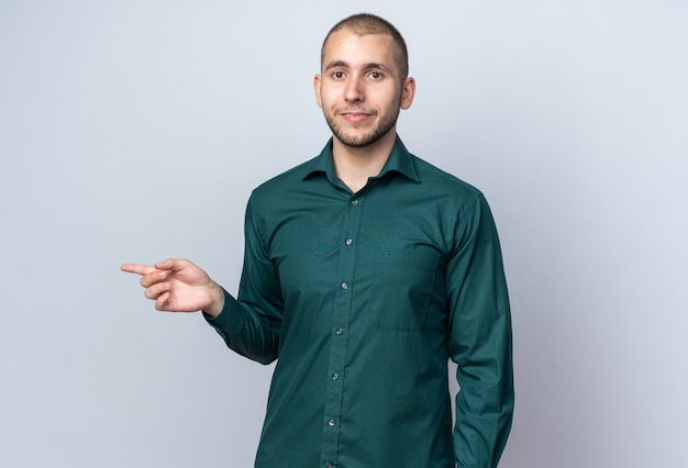 Zufriedener junger gutaussehender kerl, der grüne hemdpunkte an der seite trägt