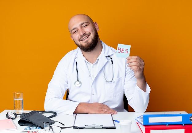 Zufriedener junger kahlköpfiger männlicher arzt, der medizinische robe und stethoskop trägt, der am schreibtisch sitzt