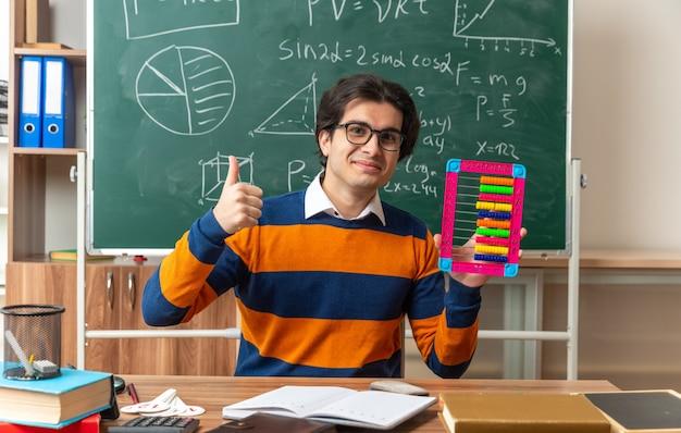Zufriedener junger kaukasischer geometrielehrer mit brille, der am schreibtisch mit schulmaterial im klassenzimmer sitzt und abakus und daumen nach vorne zeigt