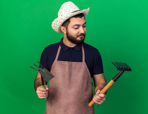Zufriedener junger kaukasischer männlicher gärtner, der einen gartenhut trägt, der hacke-rechen hält und den rechen einzeln auf grüner wand mit kopierraum betrachtet