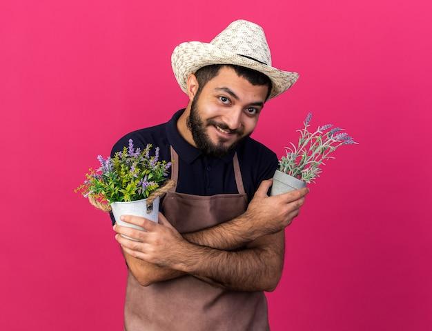 Zufriedener junger kaukasischer männlicher gärtner mit gartenhut, der blumentöpfe hält, die arme einzeln auf rosa wand mit kopienraum kreuzen