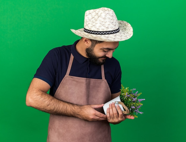 Zufriedener junger kaukasischer männlicher gärtner mit gartenhut, der blumentopf isoliert auf grüner wand mit kopierraum hält