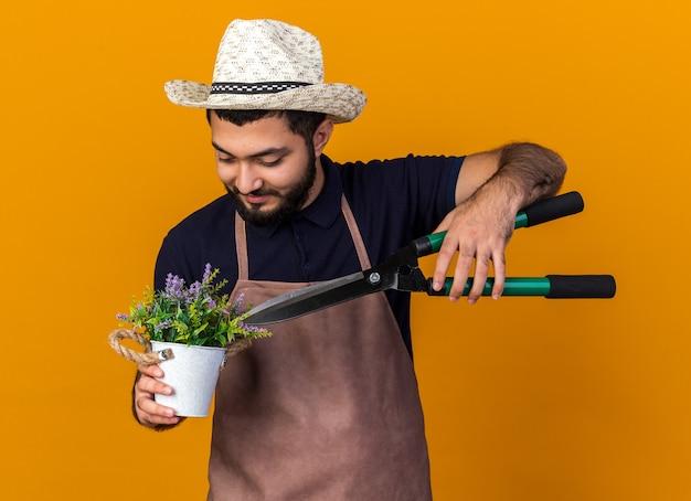 Zufriedener junger kaukasischer männlicher gärtner mit gartenhut, der eine gartenschere über blumen im blumentopf hält, isoliert auf oranger wand mit kopierraum