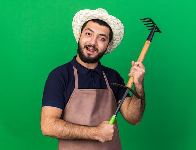 Zufriedener junger kaukasischer männlicher gärtner mit gartenhut, der rechen über hacke-rechen hält, isoliert auf grüner wand mit kopierraum