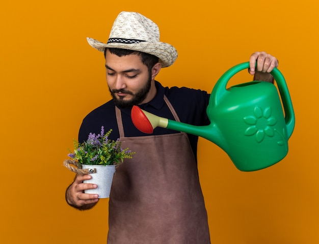 Zufriedener junger kaukasischer männlicher gärtner mit gartenhut, der vorgibt, blumen im blumentopf mit gießkanne zu gießen, isoliert auf oranger wand mit kopierraum