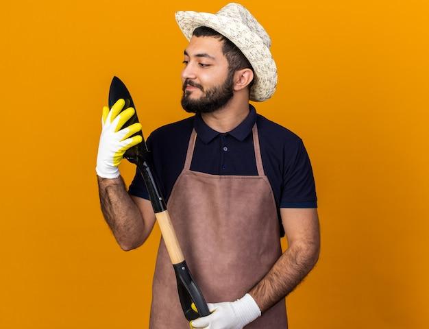 Zufriedener junger kaukasischer männlicher gärtner mit gartenhut und handschuhen, der spaten isoliert auf oranger wand mit kopierraum hält und betrachtet