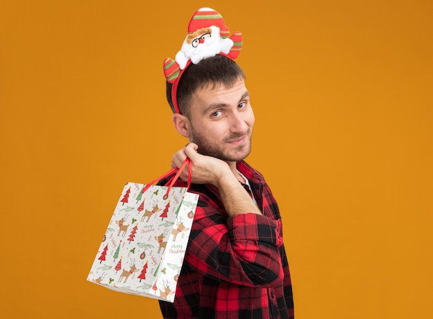 Zufriedener junger kaukasischer mann mit weihnachtsmann-stirnband, der in der profilansicht steht und weihnachtsgeschenktüte auf der schulter hält, die isoliert auf orangefarbener wand mit kopierraum aussieht
