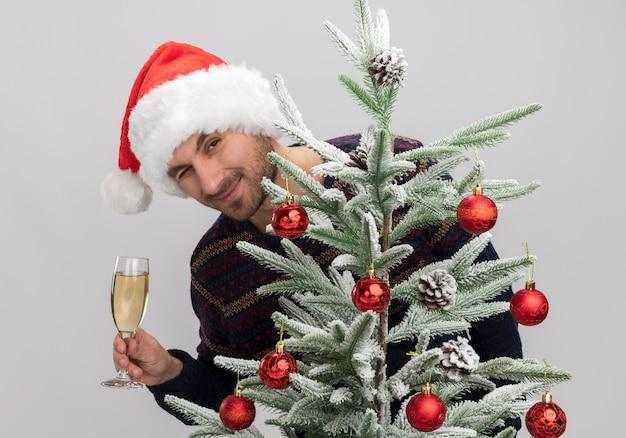 Zufriedener junger kaukasischer mann mit weihnachtsmütze, der hinter dem weihnachtsbaum steht und ein glas champagner hält, der isoliert auf weißer wand zwinkert?