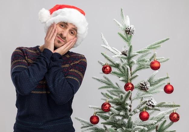 Zufriedener junger kaukasischer mann mit weihnachtsmütze, der in der nähe des weihnachtsbaums steht und die hände auf dem gesicht hält und isoliert auf weißer wand schaut
