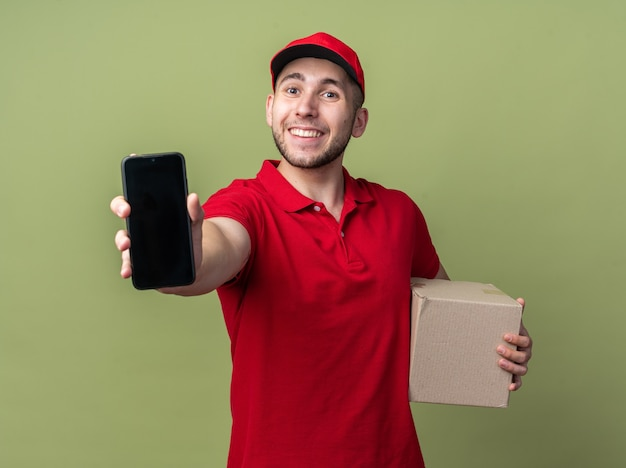 Zufriedener junger lieferbote, der uniform trägt, karton hält und smartphone zeigt