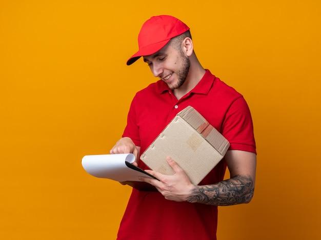 Zufriedener junger lieferbote in uniform mit mütze mit box, der die zwischenablage in der hand betrachtet