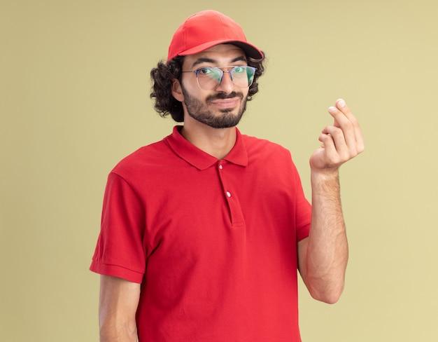 Zufriedener junger liefermann in roter uniform und mütze mit brille, der nach vorne schaut und geldgeste einzeln auf olivgrüner wand macht