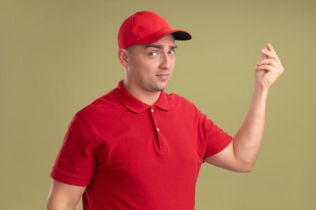 Zufriedener junger liefermann in uniform und mütze mit tippgeste isoliert auf olivgrüner wand