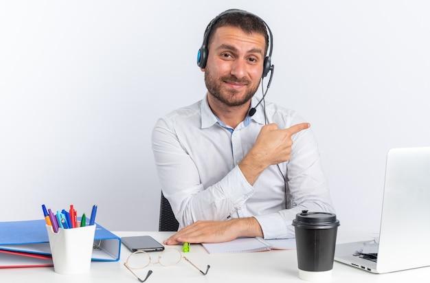 Zufriedener junger männlicher callcenter-betreiber, der ein headset trägt, das am tisch mit bürowerkzeugpunkten an der seite sitzt