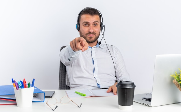 Zufriedener junger männlicher callcenter-betreiber mit headset am tisch sitzend mit bürowerkzeugen, die ihnen geste isoliert auf weißer wand zeigen